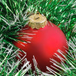 Foto Stock: Red christmas ball in green