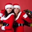 Two women in dressed as Santa, with shopping bags — Stockfoto