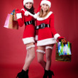 Two women in dressed as Santa, with shopping bags — Stock Photo #2009136