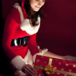 Beautiful brunette in Christmas dress opens gift — ストック写真