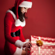 Two woman in Santa costume opening christmas gift. — Stockfoto