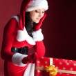 Beautiful brunette in Christmas dress opens gift — Stock Photo