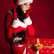 bella bruna in vestito Natale apre regalo — Foto Stock