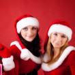 Two women in dressed as Santa, with shopping bags — Stock Photo