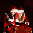 Two woman in Santa costume opening christmas gift. — Zdjęcie stockowe
