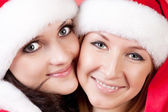 Two girl friends in christmass costumes on white — Stock Photo