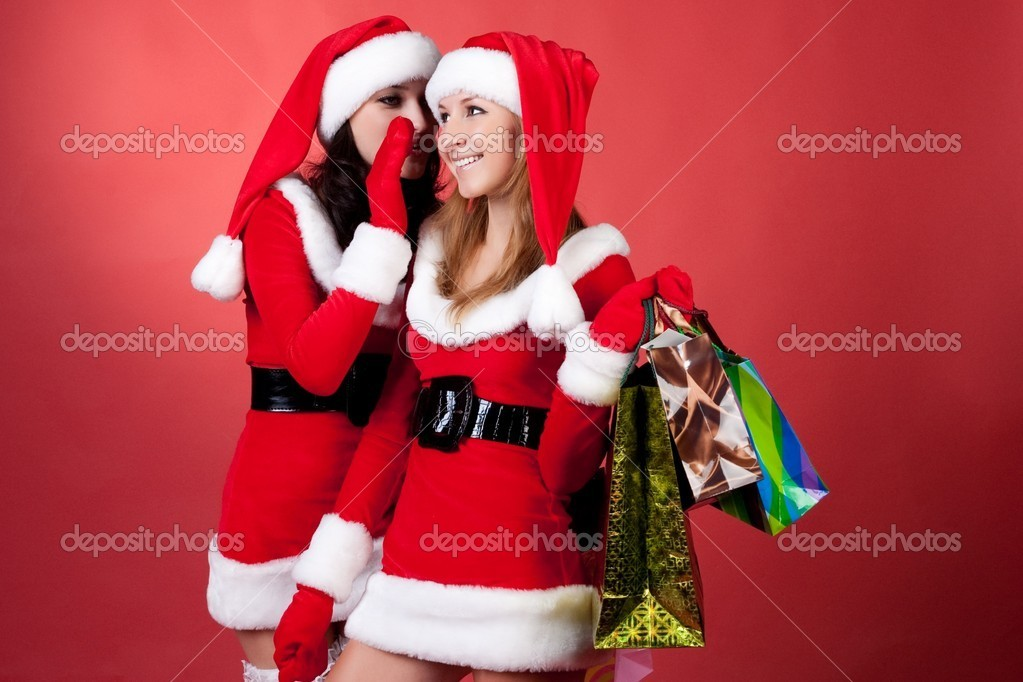 Two women in dressed as Santa, with shopping bags . on red background . — Stock Photo #2009084