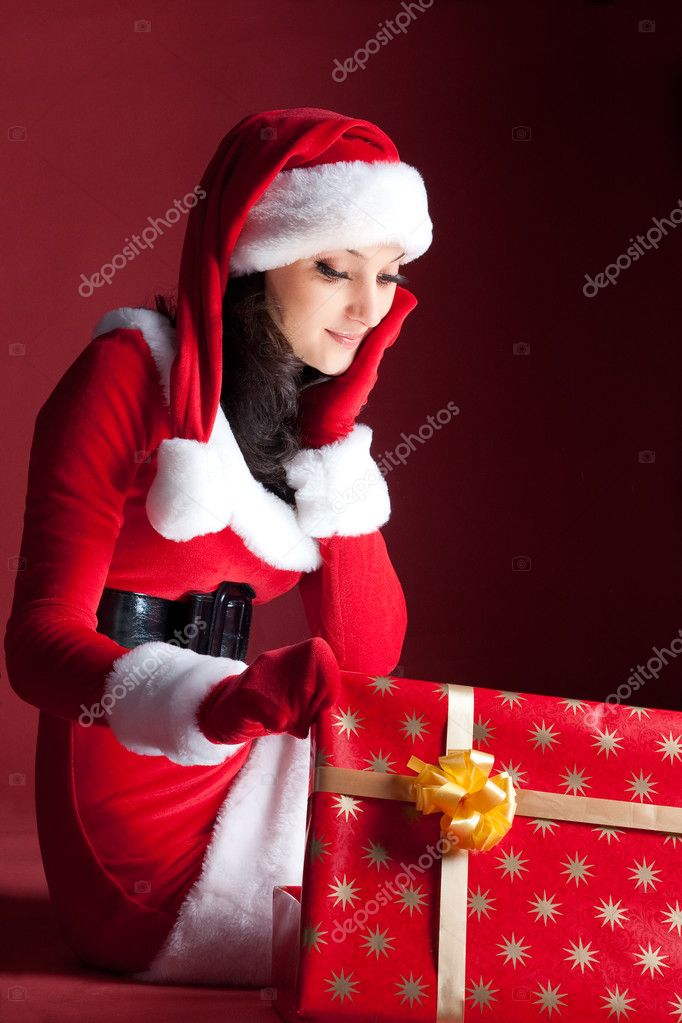 Beautiful brunette in Christmas dress opens gift. on red. — Stock Photo #2009278