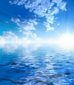 Sunny sky background and water — Stock Photo
