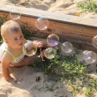 Curious baby looking at soap bubbles — Stock Photo