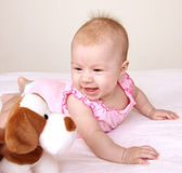 Adorable baby playing with puppy toy — Stock Photo