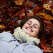 Teenage girl lying in autumn leaves - Stock Photo
