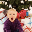 Surprised child opening gifts — Stock Photo