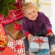 Baby looking up with christmas gifts — Stock Photo