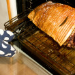 Stock Photo: Persons hand taking roast out of oven