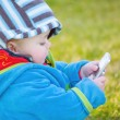 Colourful baby boy playing with mobile — Stock Photo