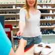 Young woman buying shoes with a credit c — Stock Photo #1460965