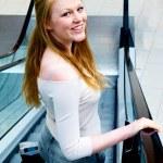 Smiling young shopper on escalator — Stock Photo