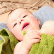 Cute baby boy lying wrapped in a towel - Stock Photo