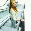 Young woman smiling happily on escalator — Stock Photo