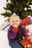 Baby sneakily opening christmas gift — Stock Photo
