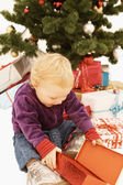 Surprised kid opening christmas gifts — Stock Photo