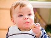 Cute little baby boy eating bread — Stock Photo