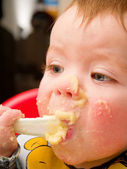 Messy baby Boy eating mashed potato — Stock Photo