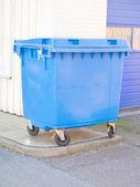 Blue plastic rubbish bin in urban area — Stock Photo