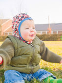 Baby boy outside sitting on grass — Stock Photo