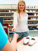 Young woman buying shoes with a credit c — Stock Photo