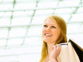 Laughing young female holding shopping — Stock Photo