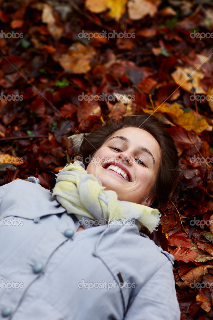 Smiling teenage girl lying in fall leaves — Stock Photo #1460375