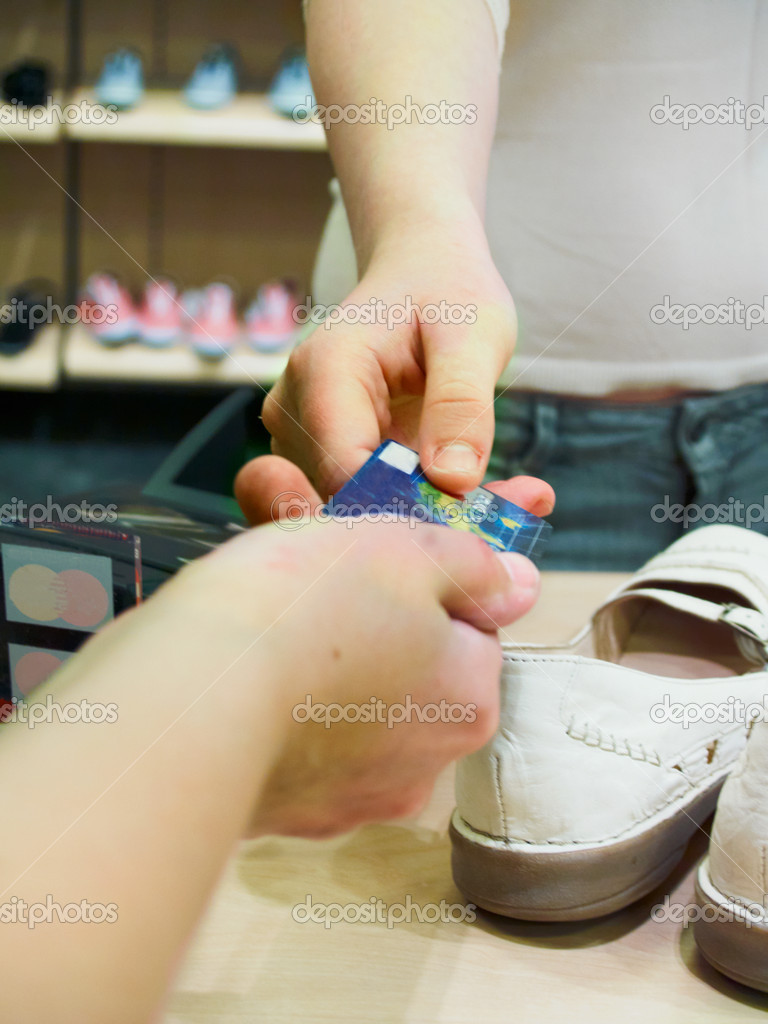 Buying shoes with a credit card in a shoe store — Stock Photo #1460969