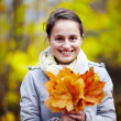 Cute young woman holding leaves — Stock Photo