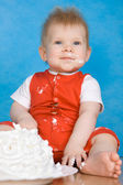 Soiled baby boy with cake — Stock Photo