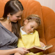 Mother and daughter reading book — Stockfoto