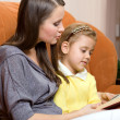 Mother and daughter reading book - Stock Photo