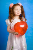 Little redhead girl with red balloon — Stock Photo