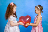 Two little girl hold red balloon — Stock Photo
