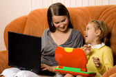 Mother and daughter using laptops — Stock Photo