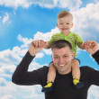 Little son sits on father shoulders — Stock Photo