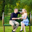 Couple in love sitting at a bench — Stockfoto