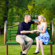 Couple in love sitting at a bench — Stock Photo