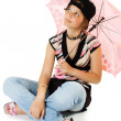 Young girl with umbrella sits on floor — Stok fotoğraf