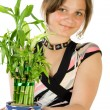 Stock Photo: Young girl with home plant bamboo