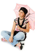 Young girl with umbrella sits on floor — ストック写真