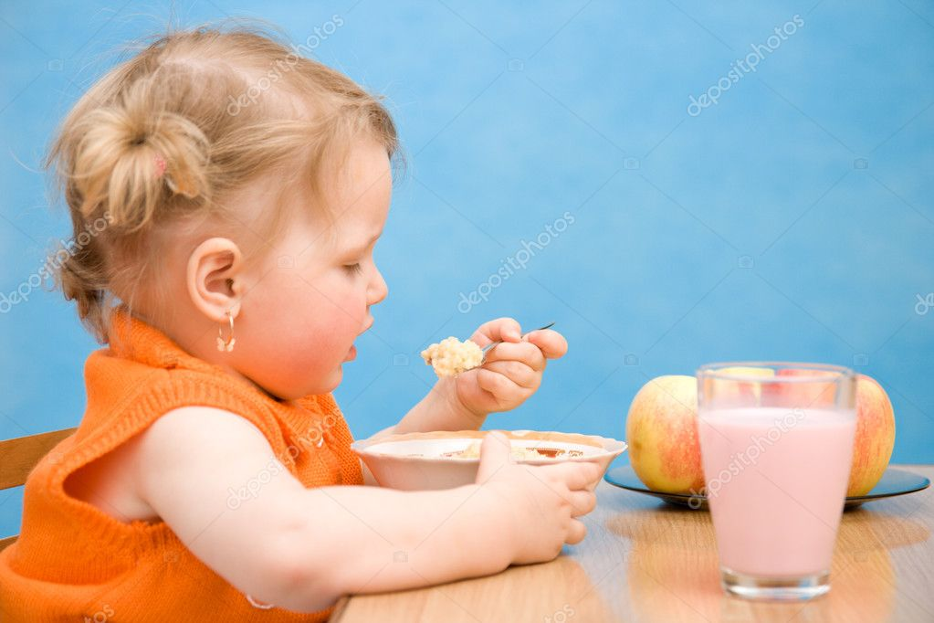 Little girl eating baby food isolated on blue background — Stock Photo #1957849