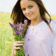 Young girl with flowers on a meadow — Stock Photo #1963572