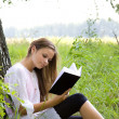Young girl reading book in park — Foto Stock